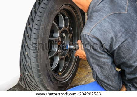 Detail image of mechanic hands with tool, changing tyre of car, with - stock photo
