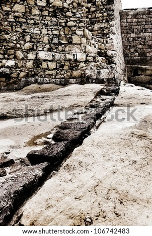 Detail image of part of the ruined walls of a coastal fort, Malta, in need of much repair. Monochrome image with sepia tint. - stock photo