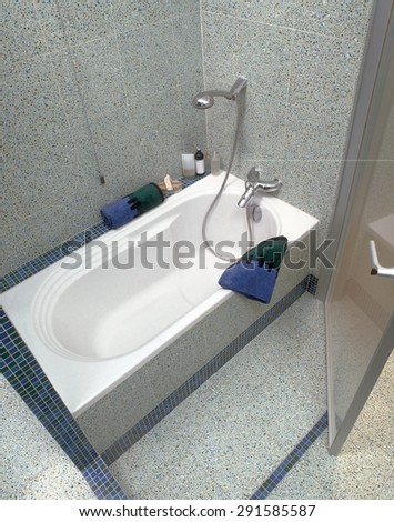 detail of a bathtub in the modern bathroom with marble floor and marble wall - stock photo