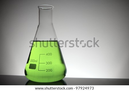 detail of a beaker with green liquid and white background - stock photo