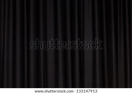 Detail of a black closed curtain in a theater - stock photo