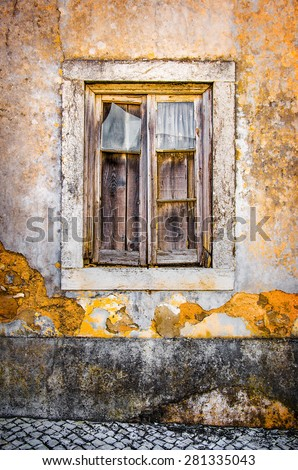 Detail of a broken window in an old yellow house ruin - stock photo