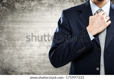 Detail of a businessman adjusting his necktie - stock photo