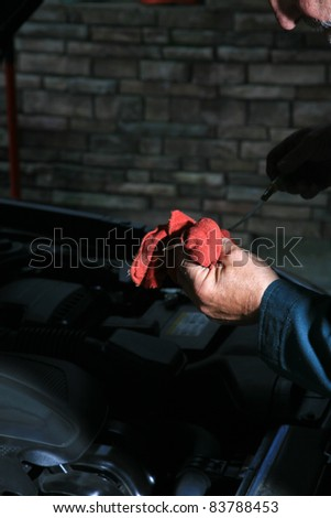 Detail of a car mechanic working on a car at the car repair shop, car in background - stock photo