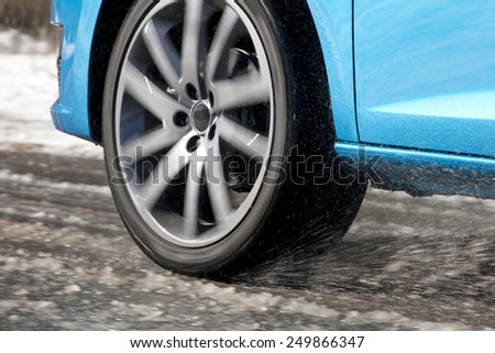 Detail of a car tire driving and splashing on the snow.  Driving on a snowy road - stock photo