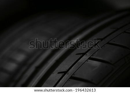 Detail of a car tire, on black. - stock photo