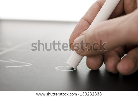 Detail of a coach hand writing a football game strategy on a board. - stock photo