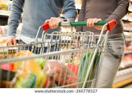 Detail of a couple shopping in a supermarket - stock photo