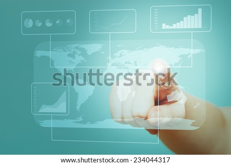 Detail of a finger displaying graphs and data on a futuristic touch screen with a global map. - stock photo