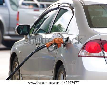 Detail of a fuel pump filling up silver car - stock photo