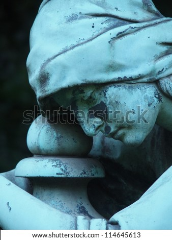 Detail of a gravestone statue showing the face of a sorrow woman - stock photo