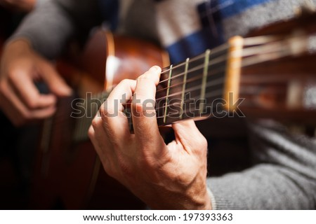 Detail of a guitarist playing a classical guitar - stock photo