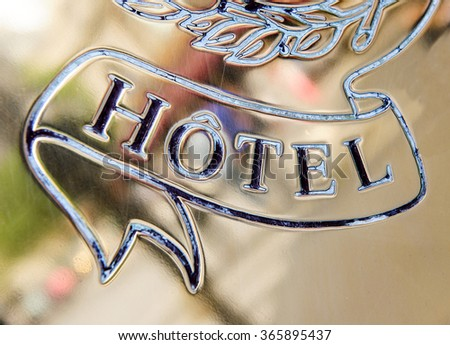 Detail of a hotel signage on gold background and beautiful engraving - stock photo