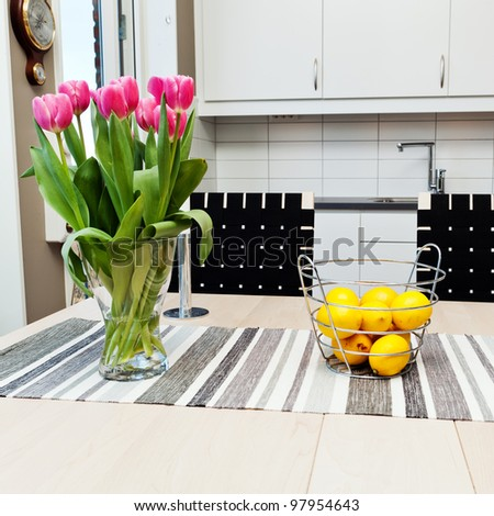 detail of a kitchen interior with a vase of tulips and a bowl of lemon in the foreground - stock photo