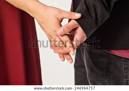 Detail of a loving couple holding hands with interlaced fingers - stock photo