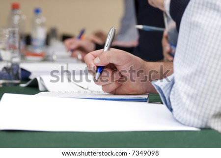 detail of a man hand  writing on a notebook with a blue pencil  and  blurred background - stock photo