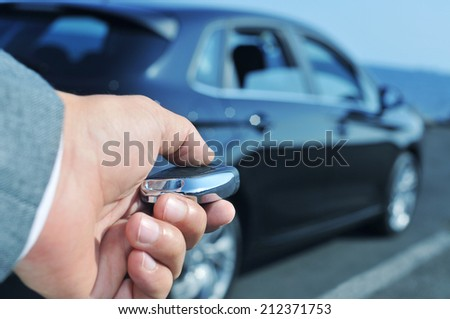 detail of a man in suit opening his car with the control remote key - stock photo