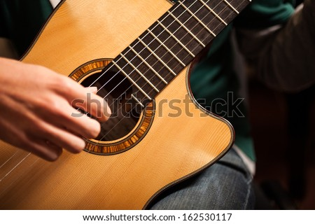 Detail of a man playing a guitar - stock photo