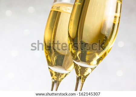 detail of a pair of flutes of golden champagne on silver bokeh background - stock photo
