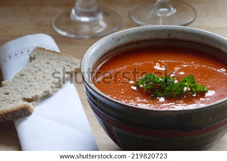 Detail of a red vegetable soup, tomato, carrot or pumpkin, in a pottery bowl with bread  - stock photo