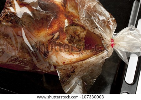 detail of a roast chicken into a broken oven bag - stock photo