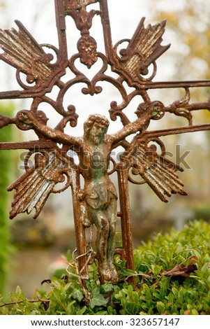 Detail of a rusty tombstone cross in a medieval French graveyard - stock photo