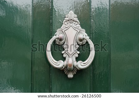 Detail of a shiny green door with a silver-colored door knocker - stock photo