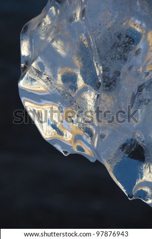 Detail of a small iceberg, known as a bergie bit.  Frozen air bubbles and cracks belie the cold, even while the sun's warmth causes drops to melt off the leading edge. - stock photo