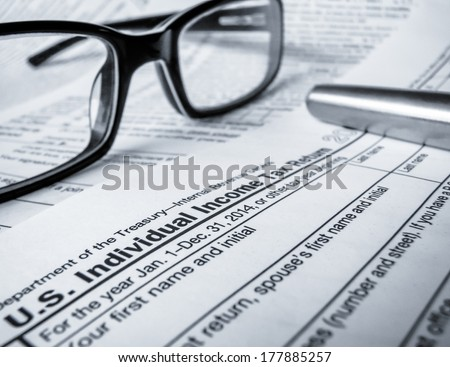 Detail Of A 2014 Tax Return With Glasses And Pen (With Shallow DoF) - stock photo