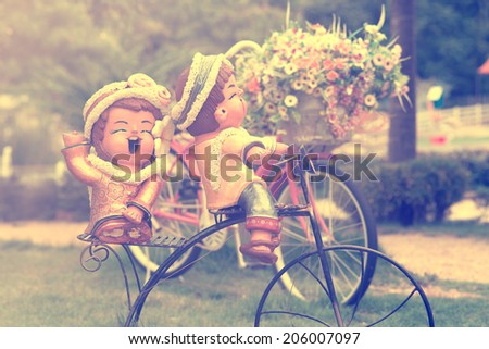 Detail of a Vintage Bicycle with wedding dolls, Bouquet of flower  (vintage color toned image) - stock photo