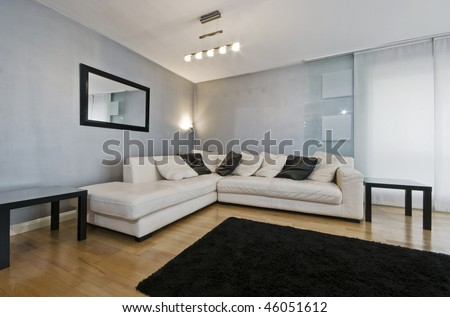 detail of a white leather corner sofa in a living room with blue metallic wall paint - stock photo