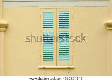 detail of a wooden window with shutters close on yellow wall - stock photo