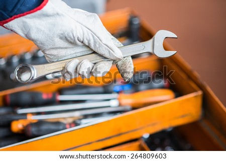 Detail of a worker's hand in a factory - stock photo