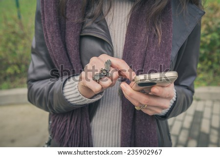 Detail of a young woman with ring texting in the city streets - stock photo