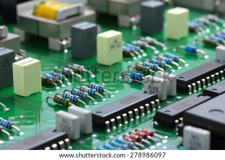 Detail of an electronic printed circuit board with many electrical components-(soft fogus) - stock photo