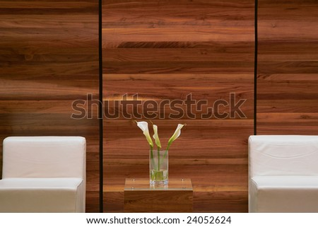 Detail of an elegant waiting room with wooden panel and white armchair - stock photo