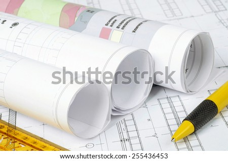 detail of an engineer workplace table with plans on paper and instruments - stock photo