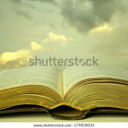 Detail of an old holy bible open with a beautiful and mystical sky in the background in a golden light - stock photo