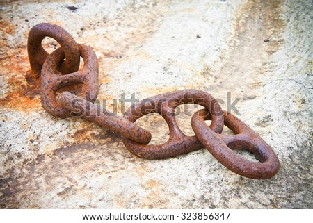 Detail of an old rusty metal chain anchored to a concrete block - stock photo