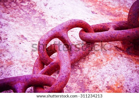 Detail of an old rusty metal chain anchored to a concrete block - toned image - stock photo