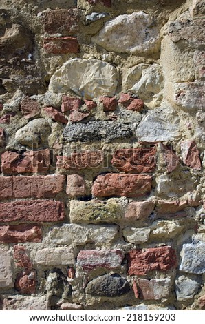Detail of an old stone wall in the multi-colored facade of the ancient house - stock photo