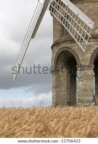 Detail of an old stone windmill in a field of wheat - stock photo