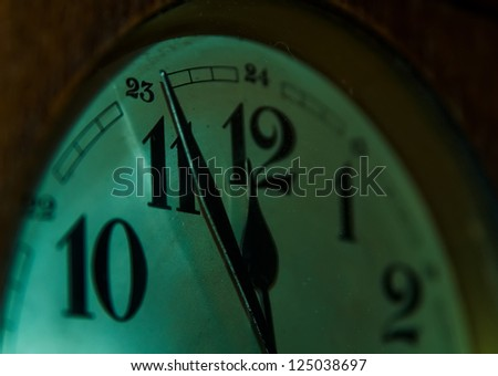 Detail of an old wall clock showing five to twelve. - stock photo