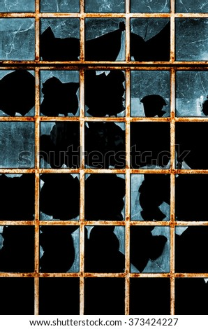 Detail of an old window with rusty iron frames and broken glass - stock photo