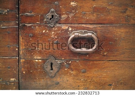 detail of an old wooden door with two strange patches for keys - stock photo