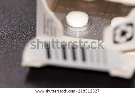 Detail of an opened cardboard package with a blister of tablets. - stock photo