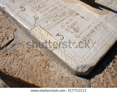 Detail of ancient stone dial sundial closeup. On the white marble slab engraved numbers and names of the months in Russian - stock photo