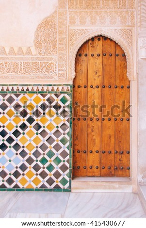 Detail of archway, wall tiles and decorative Islamic calligraphy on the walls of the Alhambra, Granada (Spain) - stock photo