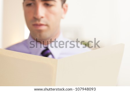Detail of attractive young business man looking at file with serious expression wearing a purple shirt and tie. File is in focus, face is out of focus. - stock photo