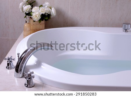 detail of bathroom, white bath tub with faucet and beige tiles, selective focus - stock photo